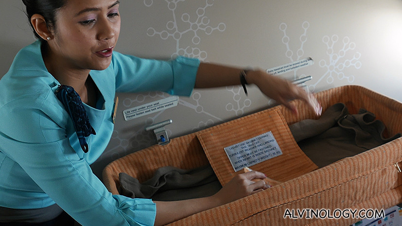 A SilkAir stewardess setting up a bassinet for a baby seated in front of us
