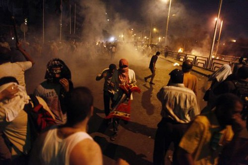 Egyptians flee after the army opened fire on demonstrators outside the Republican Guard headquarters in Cairo. At least 42 people have been reported killed and 322 injured. by Pan-African News Wire File Photos