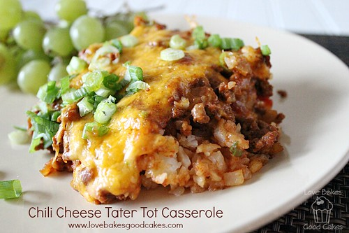Chili Cheese Tater Tot Casserole close up on plate with green onions and green grapes.