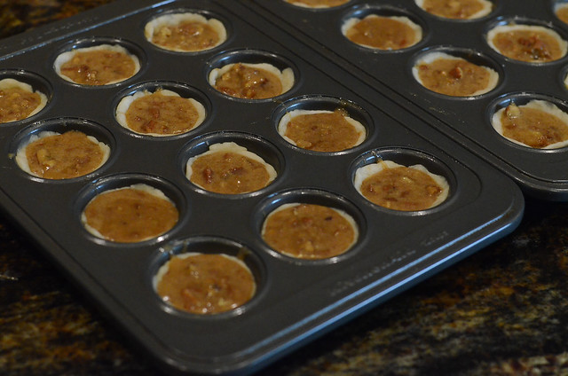 Pecan filling is added to dough in a mini muffin pan.