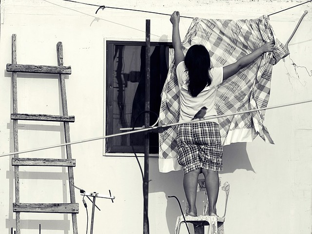 Woman hanging blanket. Photographed by Bernard Eirrol Tugade