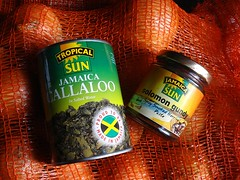 "A can with a picture of dark green vegetables and the words ""Tropical Sun / Jamaica Callalo / in Salted Water / Proud To Be Made In Jamaica"" next to a jar with the words ""Jamaica Sun / solomon gundy / Spicy Smoked Herring Paste"".  Both can and jar sit on top of a orange plastic mesh sack of onions, which fills the whole frame."