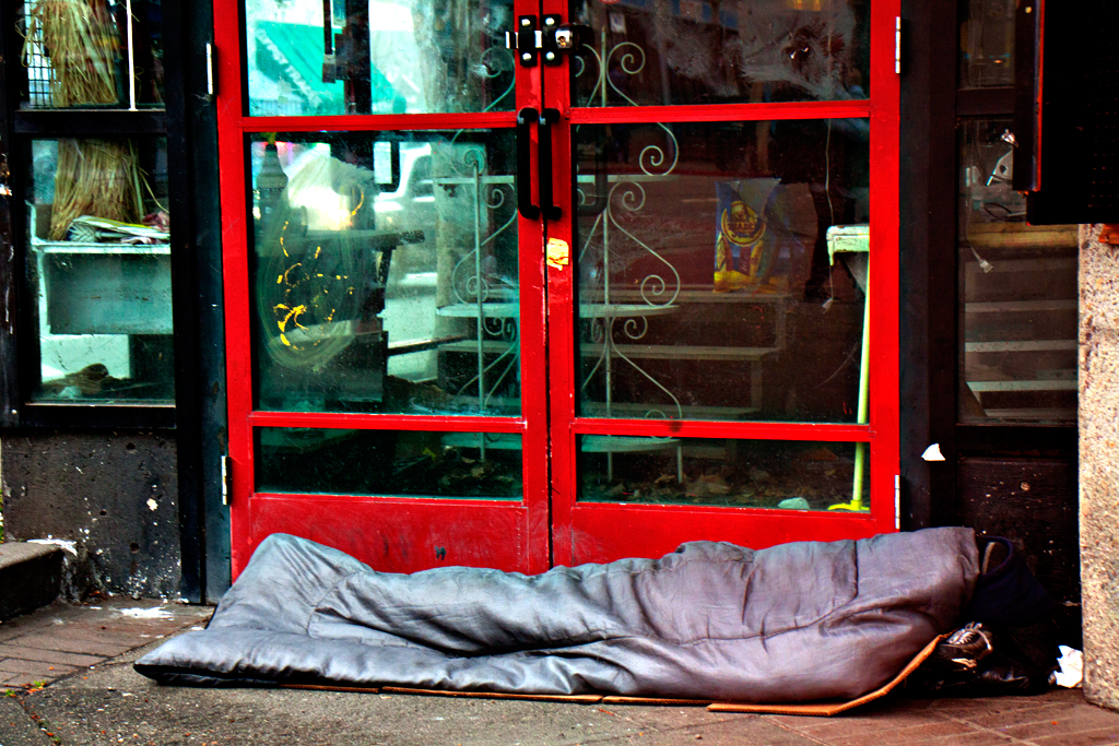 Sleeping-person-outside-red-framed-doors-in-3-13--Berkeley