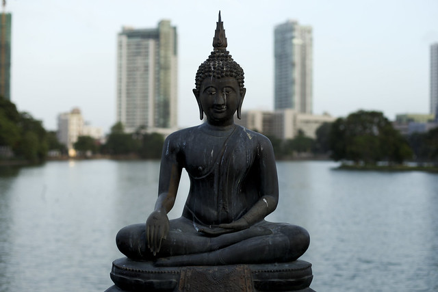 Buddha statue with modern buildings in the back