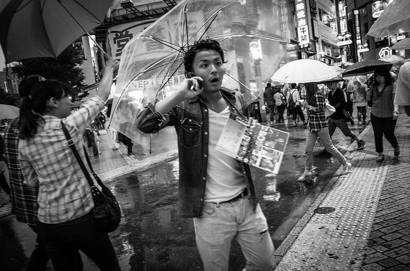 Man with transparent umbrella on the phone at Shibuya crossing.