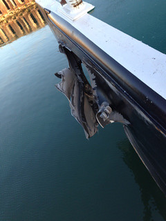 A gash in the hull of a barge is the result of a collision between the tugboats Yellowfin and Capt. Warren that occurred in the Corpus Christi ship channel, Dec. 17, 2013. Coast Guard Sector Corpus Christi has dispatched marine investigators to determine the cause of the collision. U.S. Coast Guard photo.