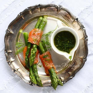 Asparagus wrapped in smoked salmon with dill sauce on metal plate