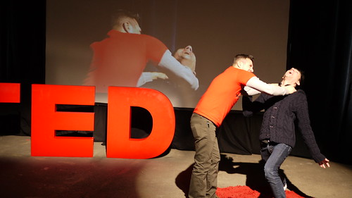 One guy strangling another at a TED Talk.