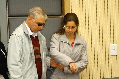 Descrição da imagem: Na foto, a estagiária de jornalismo do gabinete do Vereador Raul Cassel, Bruna Matana, conduz o presidente da Adevis, Ricardo Sewaald, à tribuna de honra. Fim da descrição.