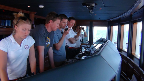 On the bridge of the White Rose, from left to right, are crewmember Sammy, graduate student Ken Pesyna, Professor Todd Humphreys, Captain Andrew Schofield, and crewmember Ryan. The bridge houses the ship's GPS receiver, RADAR and chart display, and engine and steering controls.