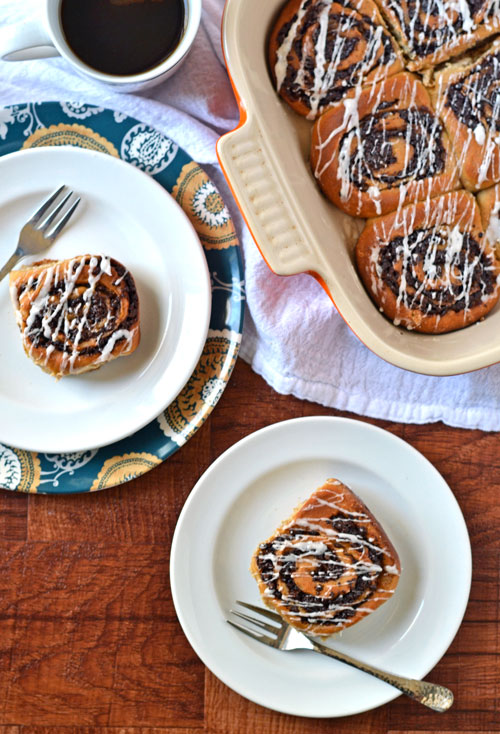 Chai cinnamon rolls in a baking dish and on two white plates