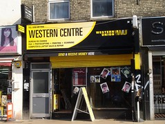 "A terraced shopfront in black and yellow, with a tall A-board standing outside.  The frontage reads: ""Western Centre / Western Union / WU / Bureau de change / Fax / Photocopying / Printing / Scanning / Computer & Laptop Sales & Repair"".  There are various hairdressers' headshots in the front window."