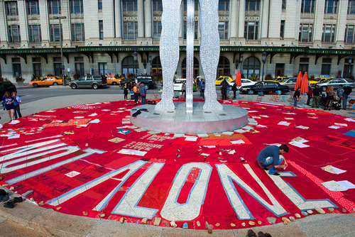 "A red quilt placed on the plaza of Baltimore's Penn Station reads ""Not Alone."""