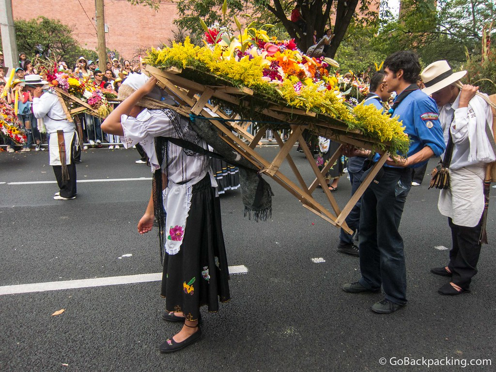 A silletera receives assistance carrying her flower display