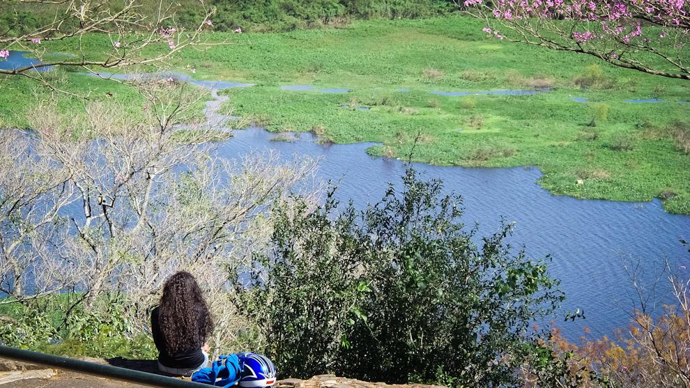 Una mujer se aparta para contemplar la vista del Río Paraguay desde la cima del Cerro Lambaré (Elton Núñez).
