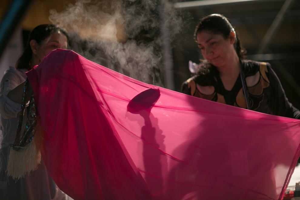 Dos mujeres planchan al vapor una de las prendas para el siguiente desfile en la Conmebol, durante el Asunción Fashion Week. (Tetsu Espósito)