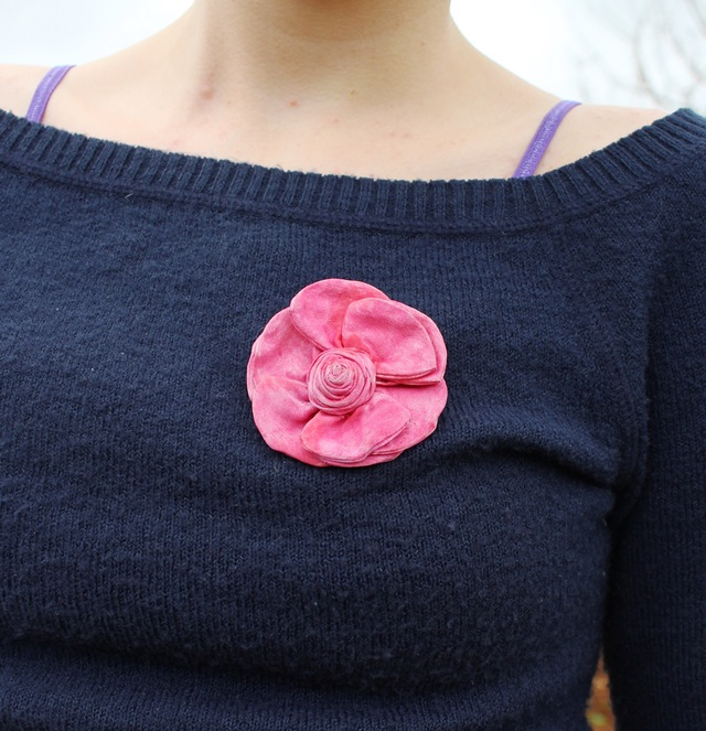 pink rose brooch on navy blue sweater