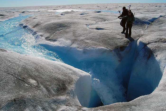 A stream of meltwater on the surface of the Greenland Ice Sheet enters a moulin connecting to the glacier's bed, 700 meters below.  Surface meltwater lubricates the bed and temporarily speeds up the ice sheet's movement toward the sea every summer. From left, Blaine Morriss (Dartmouth College) and Lauren Andrews (University of Texas). Location: west coast of the Greenland Ice Sheet.