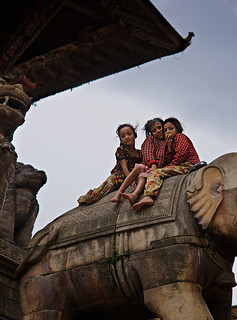 Little Nepali girls sitting on elephant statue in hinduist temple, Bhaktapur, Nepal