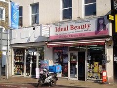 "Two terraced shopfronts seen on a sunny day.  The one on the left is at the corner of the terrace, and the frontage sign has been painted over in white.  The one on the right has a sign reading ""Ideal Beauty"" in large letters and ""Hair Care"", ""French Cosmetics"", ""Wigs, Hair Extension, Pony Tail, Accessories, Skin Care"", and ""Ideal Hair & Beauty Salon"" in smaller letters around it.  Both shops have fully glazed fronts, and the doors of both are open."
