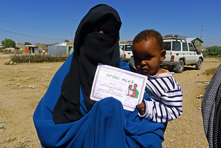 Hibo Abdikarim Ibrahim proudly shows the vaccination certificate for her son