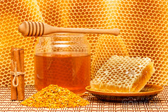 Honey in jar with dipper, honeycomb, pollen and ci…