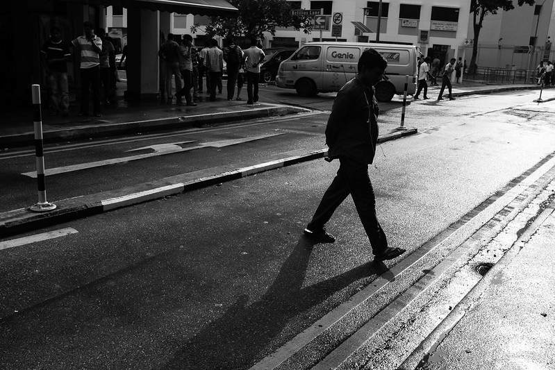 A man crossing a small road at Little India, Singapore