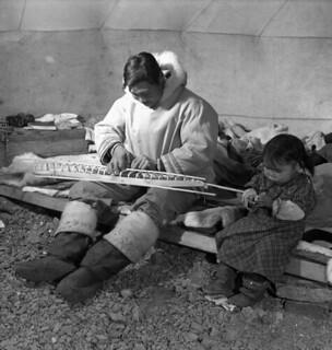 Inuit man, Salomonie, working  on a model kayak for the Canadian Handicrafts Guild, with his daughter, Annie, at his side, Cape Dorset, Northwest Territories / Un homme inuit, Salomonie, construit une maquette de kayak pour la Guilde canadienne des m