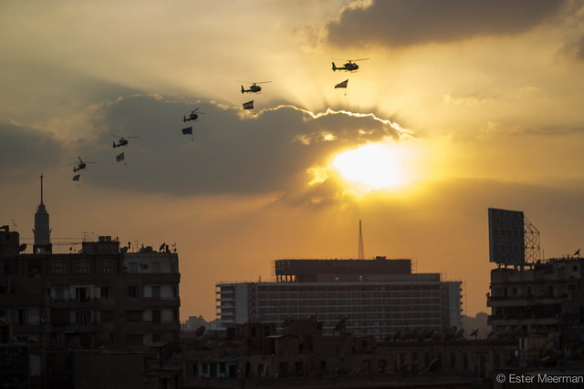 Army choppers circling Tahrir square carrying big flags