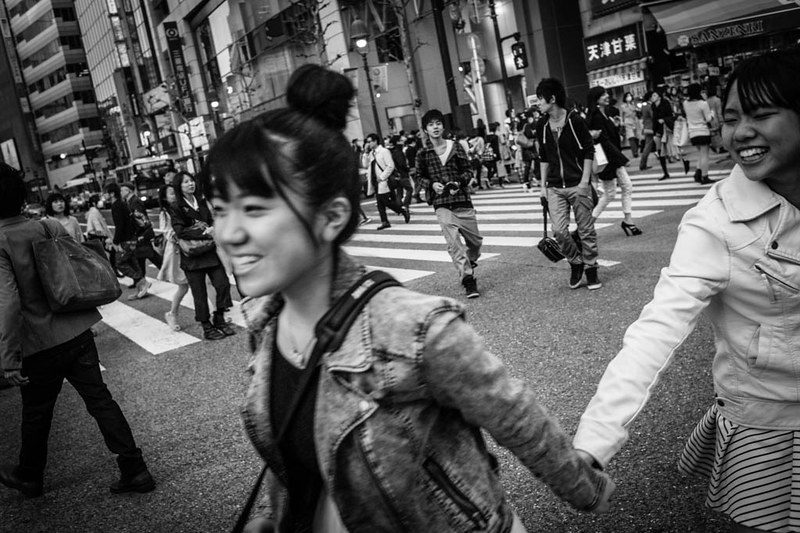 Two girls crossing Shibuya Crossing.