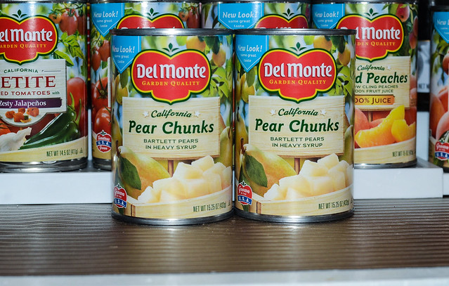 A close up two cans of Del Monte Pear Chunks.