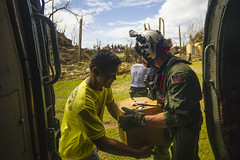 Naval Aircrewman (Tactical Helicopter) 3rd Class William Casson takes supplies from an SH-60B Seahawk from Helicopter Anti-Submarine Squadron Light (HSL) 49, assigned to USS Cowpens (CG 63), and gives them to a disaster victim, Nov. 17. (U.S. Navy photo by Mass Communication Specialist 3rd Class Ricardo R Guzman)