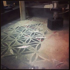Tesselated truncated tetrahedron coming to life via water jet.  Each hexagonal side is over 800 inches of cutting with this pattern.  Water jets cut by blasting garnet sand through metal in a high pressure stream of water.  Infinite thanks to Ike for his