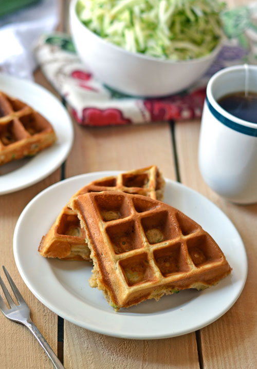 Waffles made with zucchini on two plates next to a cup of tea