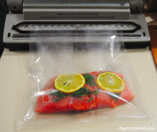 Vacuum sealing the salmon with some salt, dill and slices of Meyer lemon