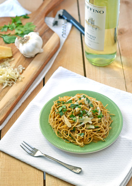 A green plate with pasta next to a bottle of white wine