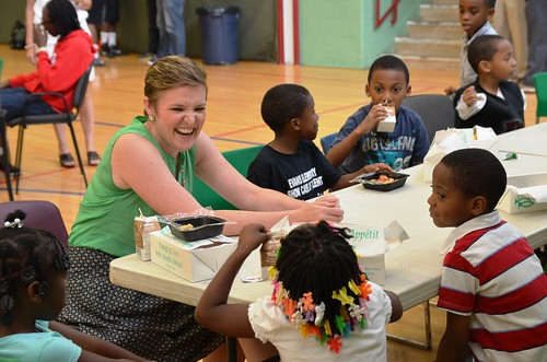 The Director of USDA's Center for Faith-Based and Neighborhood Partnerships, Norah Deluhery, eats lunch with kids at a Philadelphia Archdiocese's Nutritional Development Services (NDS) summer food service site.  The Center maintains integral relationships with partners like NDS to ensure disadvantaged children don't go hungry when school is out.