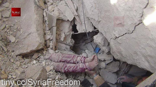 Picture of bottom half of a child under the rubble caused by ASSad death barrels