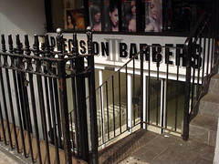 "A basement shopfront with a fully glazed front and a sign reading ""Precision Barbers"" in black capital letters on a white background with grey detailing.  Metal steps lead down from street level, with black railings separating them from the pavement."