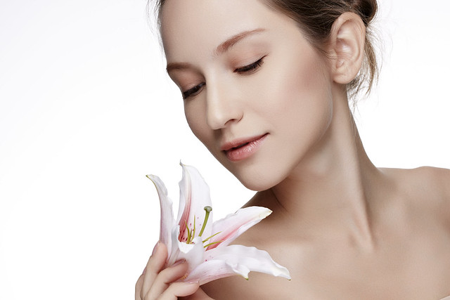 Beautiful woman with clean healthy skin with flower