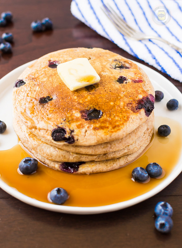 whole wheat buttermilk pancakes stack with butter sitting in puddle on syrup on plate
