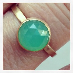 Green and gold ring on a giant finger