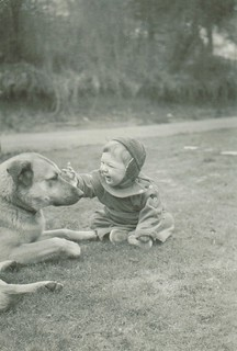 The baby looks happier than the dog