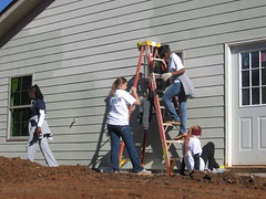 Auburn University and University of Alabama students paint the outside of a Habitat for Humanity home for a Lee County family. Students are working to finish the home in time Christmas.