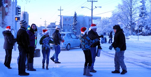 Community volunteers wearing Santa Claus hats - out to spred Christmas joy to the world - distributing hot cider, cookies, candy, and other goodies to passerbys, on a cold snowy day, Anchorage, Alaska, USA by Wonderlane