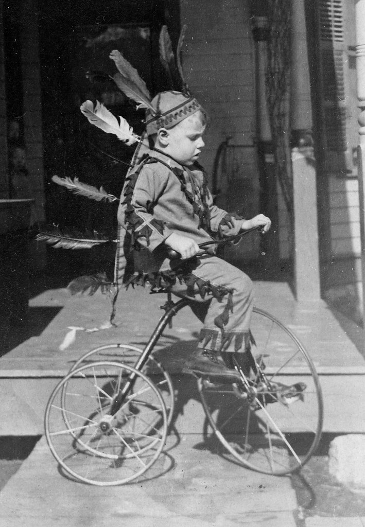 Playing in a head dress on a tricycle.