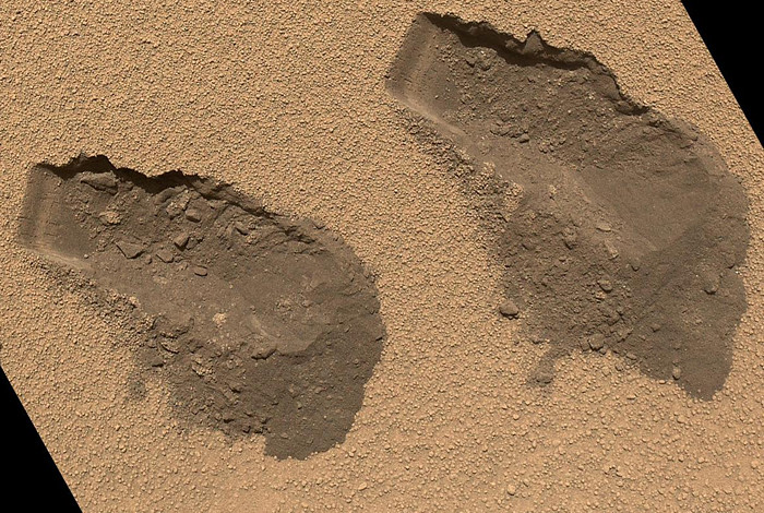 "This image shows two areas on Mars in a location named Rocknest that were scooped out by the Curiosity Rover last year. Researchers took samples of the areas to determine whether they were wetter underneath or whether they dried out after scooping. Researchers found that soil moisture was consistent at the surface and underneath. Nevertheless, there is a small amount of water in the soil that astronauts might be able to use to sustain themselves. These finding and others are outlined in a series of papers appearing today in the Journal ""Science."" (Image credit: NASA)"