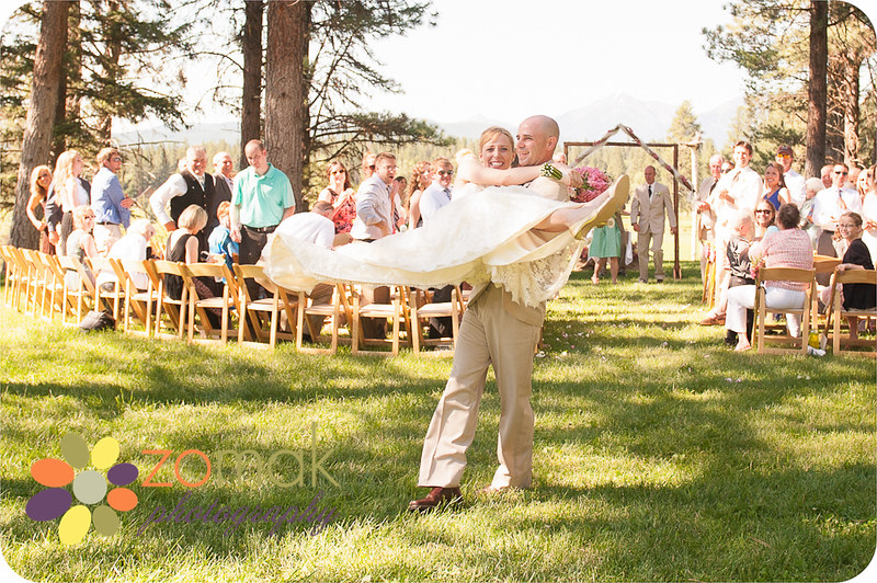 The groom sweeps his bride off her feet after leaving their wedding ceremony at Seeley Lake.