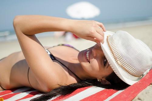 ragazza sdraiata al sole che tiene con la mano un cappello sulla testa