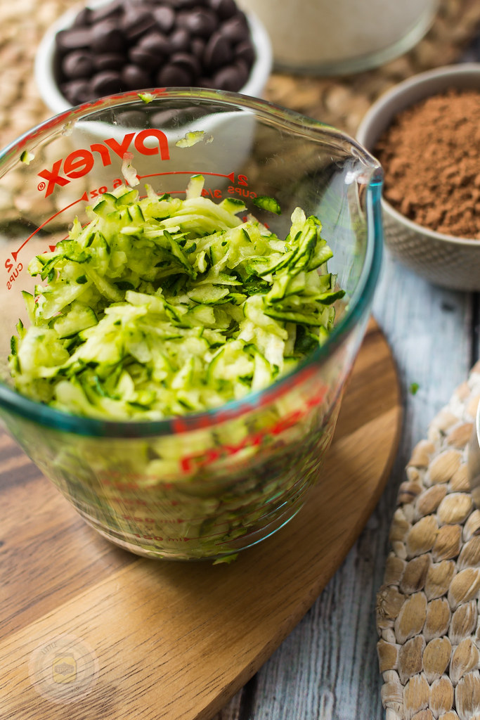 close up of Shredded Zucchini in a measuring jar on a wooden board